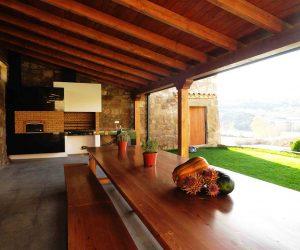 Mesa donde comer y cenar cerca de la barbacoa en el porche de madera en Casa Rural la Torra de Ribelles